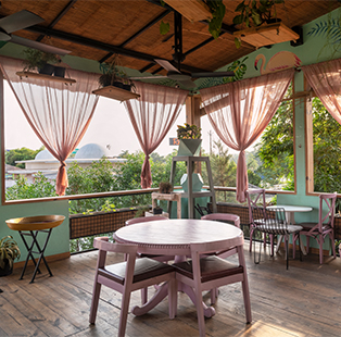Designed by Studio Clay, the Biscuiteers bakery next to a busy highway in Meerut surprises with its arboreal atmosphere